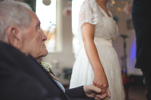 Bride holding hand of Grandad during wedding ceremony
