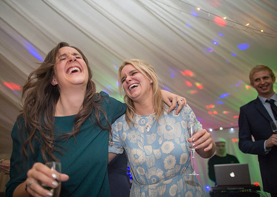 Two weddings guests laughing whilst on the dance floor