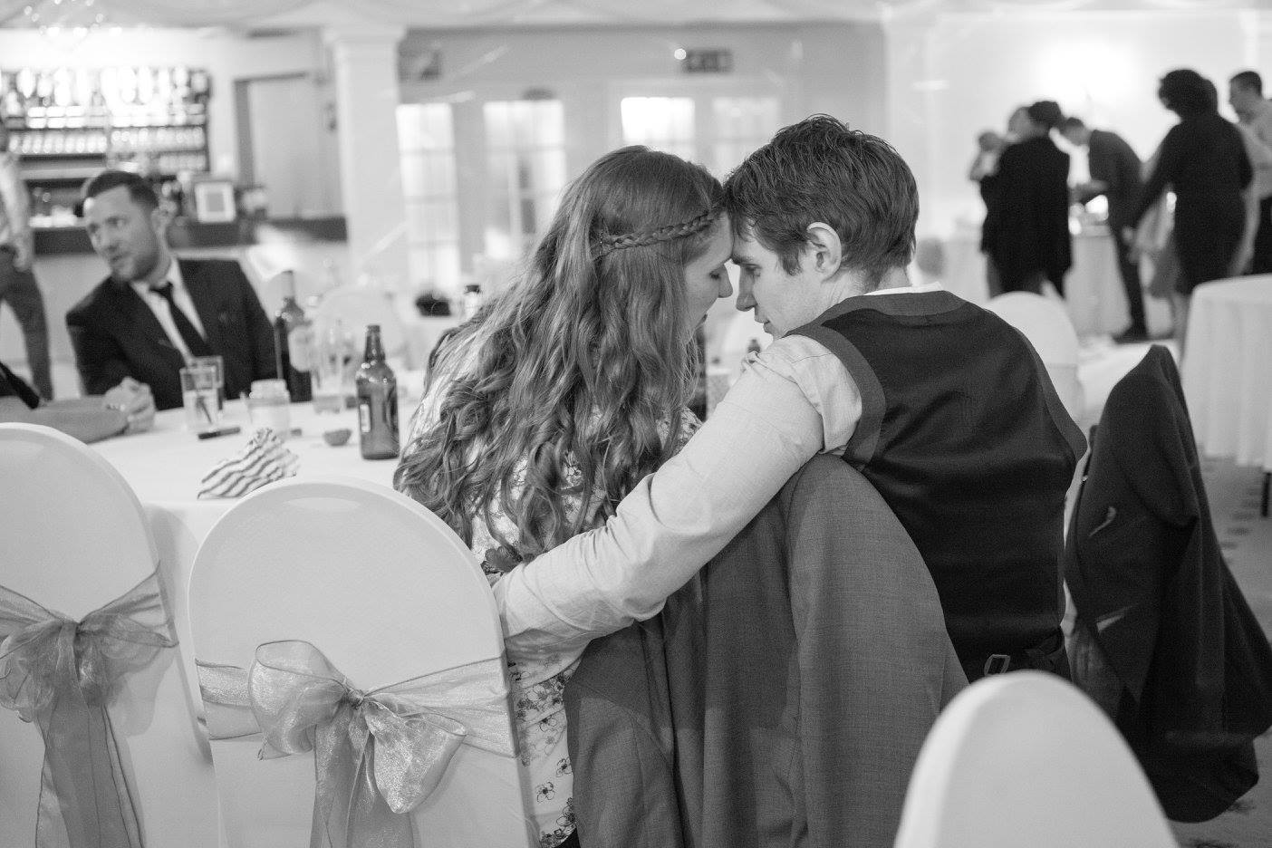 Black and white photo of wedding guests being close