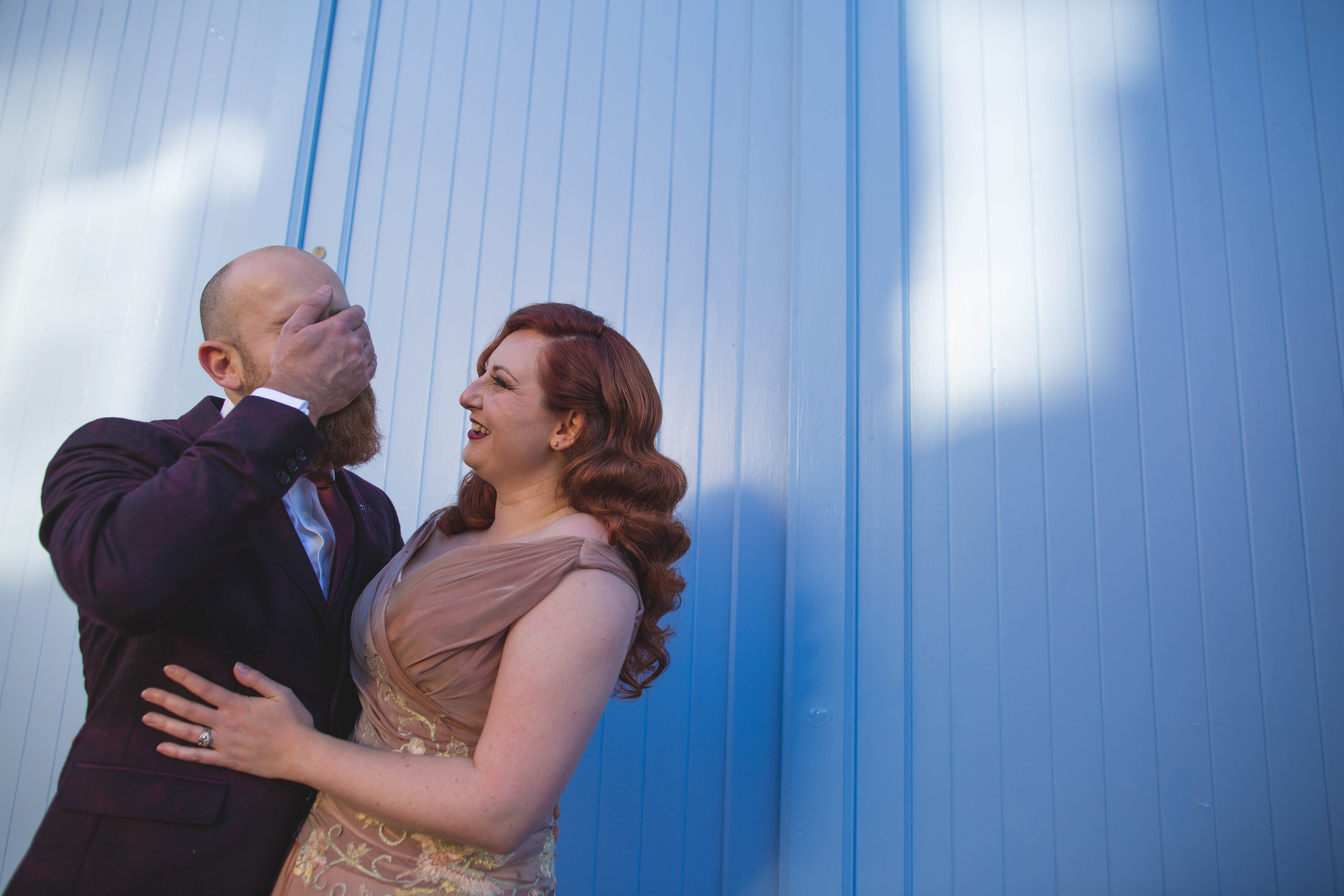 groom covering face laughing with bride