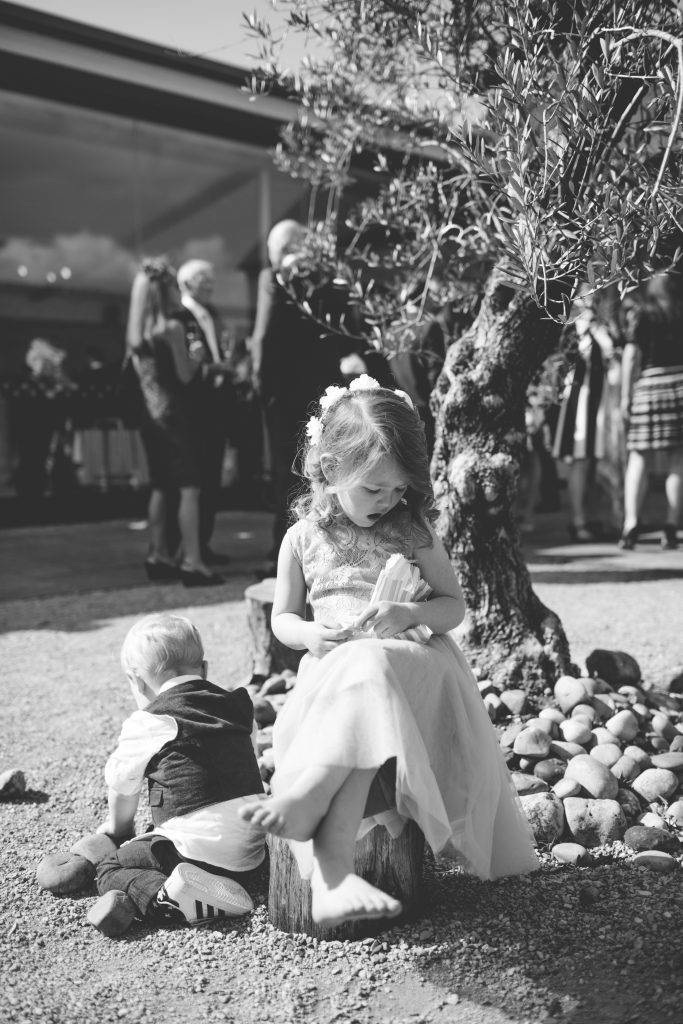 flower girl sat under tree at swallows nest barn