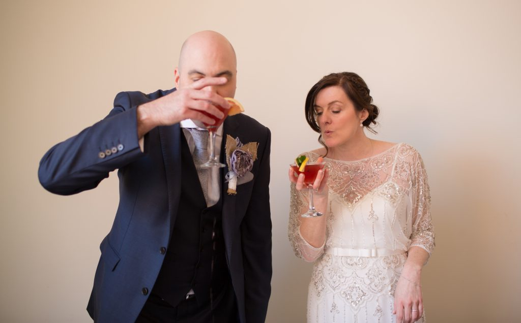 bride and groom sipping cocktails