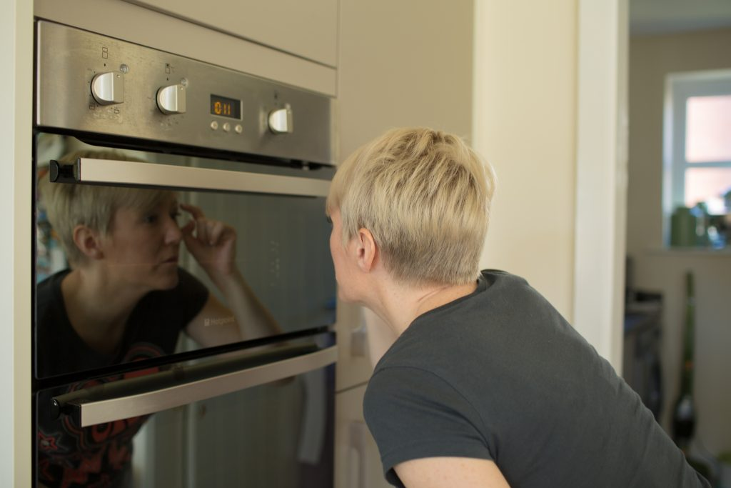 maid of honour checking eyelashes in oven door