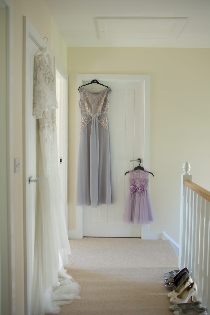wedding dress and bridesmaid dress hanging up