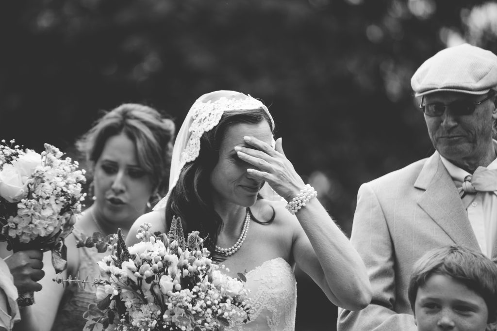 black and white photo of bride with hand to face