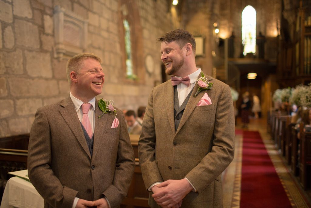 photo of groom and best man laughing in church