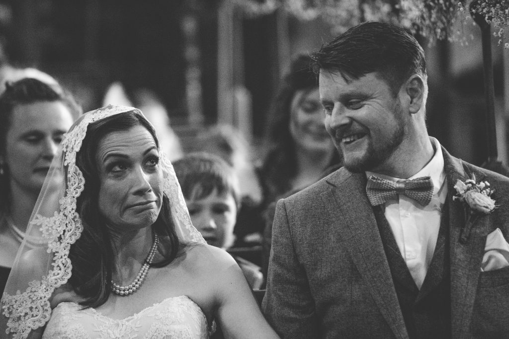 black and white photo of bride and groom in church