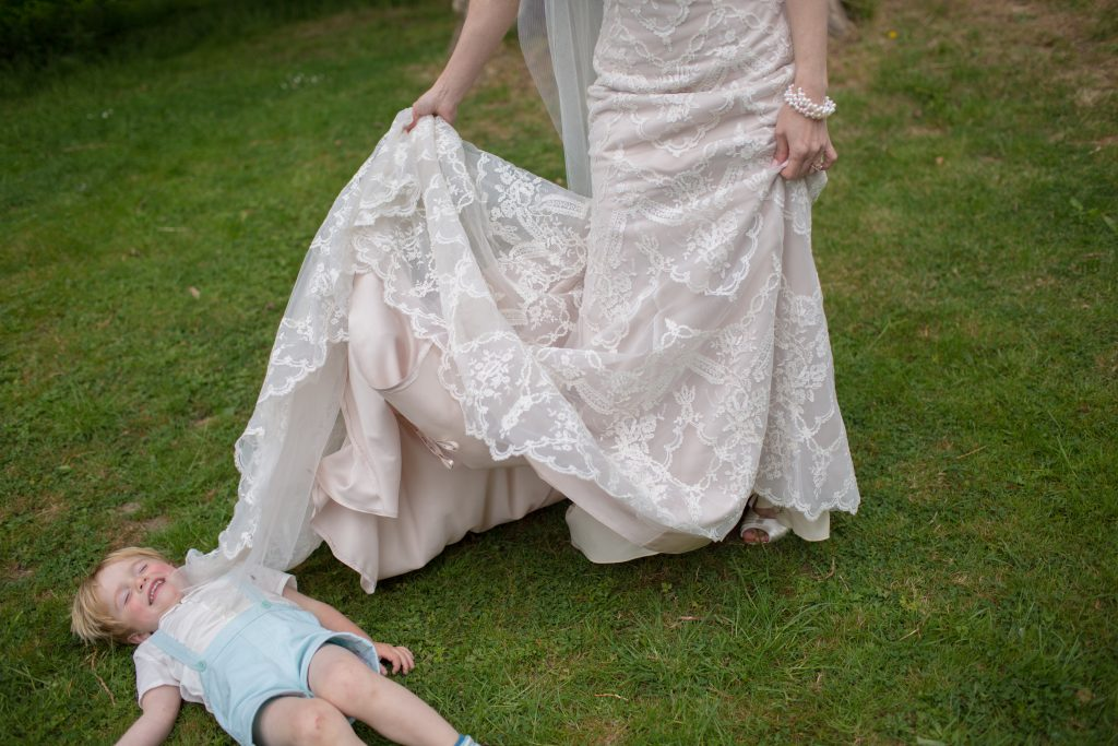 bride lifting wedding dress over young guest