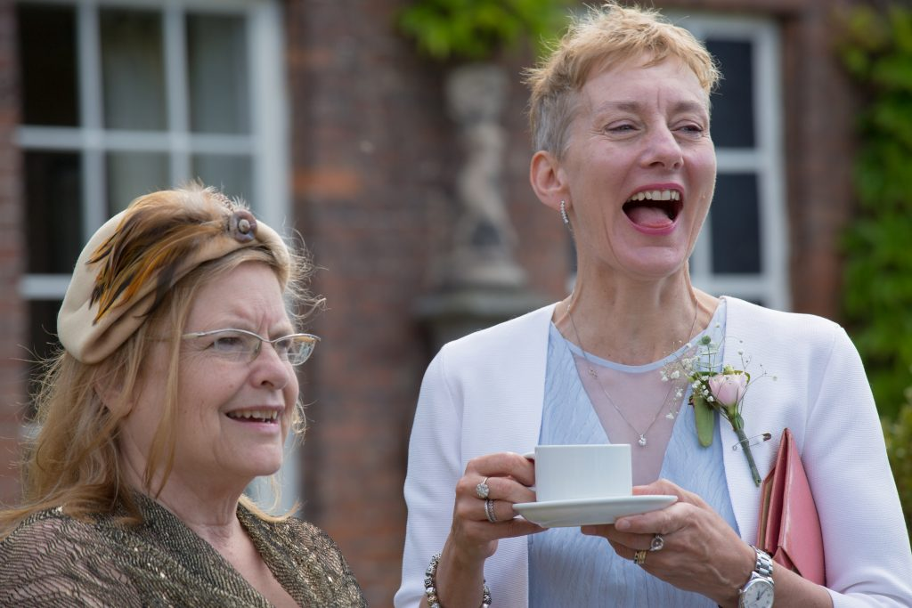 two wedding guests laughing