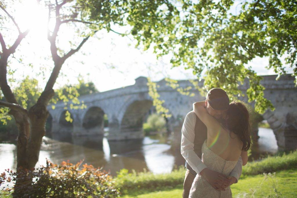 newly married couple doing first dance by river