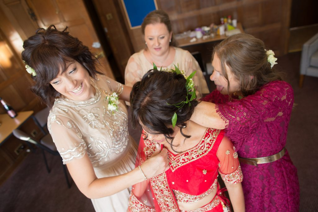 bride being helped to get ready by bridesmaids