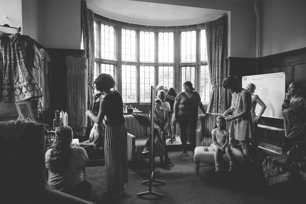 black and white photo of bride in room with bridesmaids