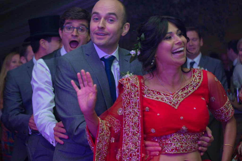bride and groom during conga round the marquee