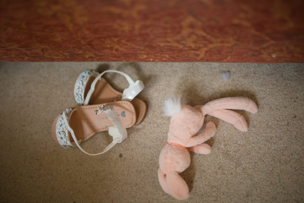 flower girls sandles and soft toy on floor