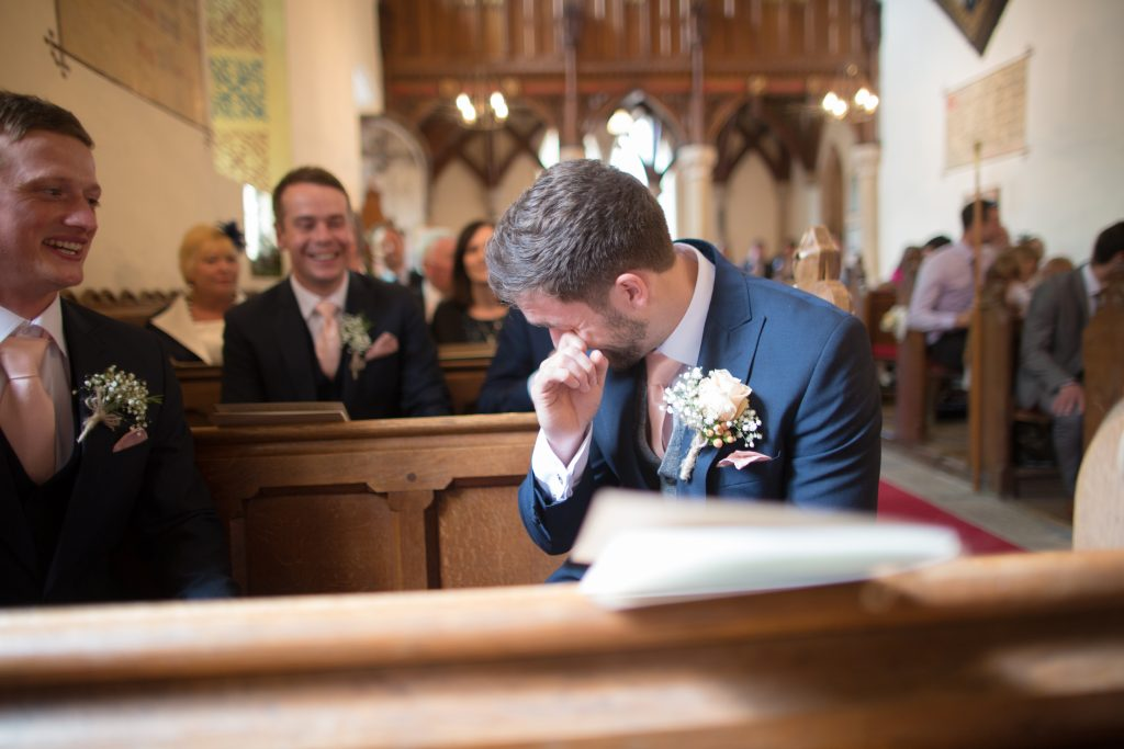 emotional groom waiting fir bride in church