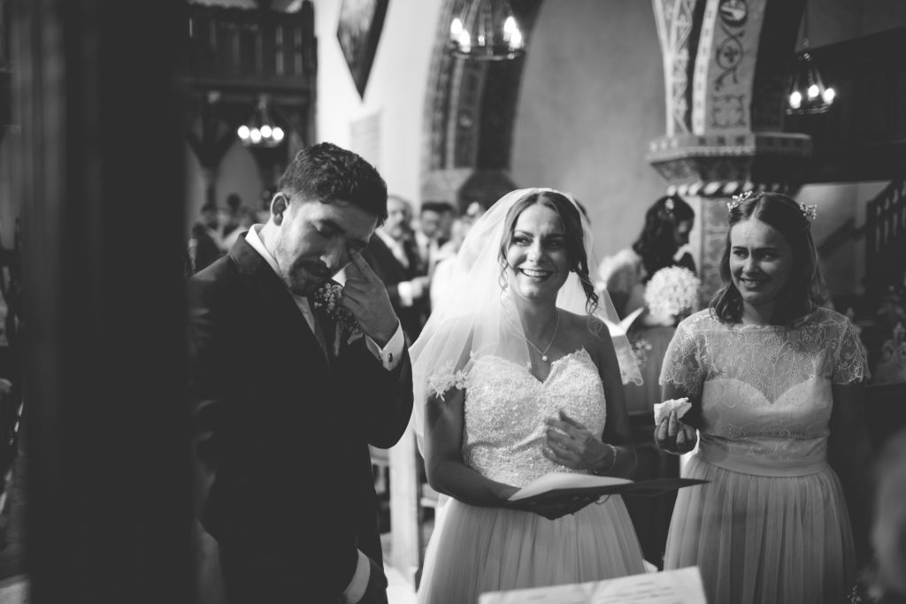 groom wiping tear away during wedding service