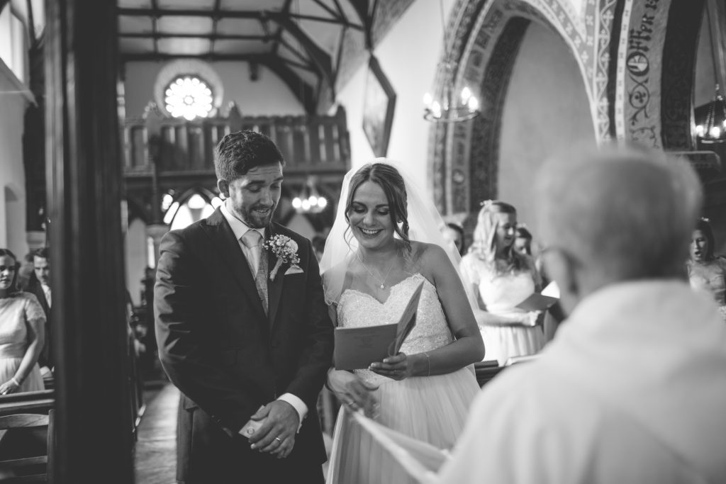 black and white photo of bride and groom sharing order of service