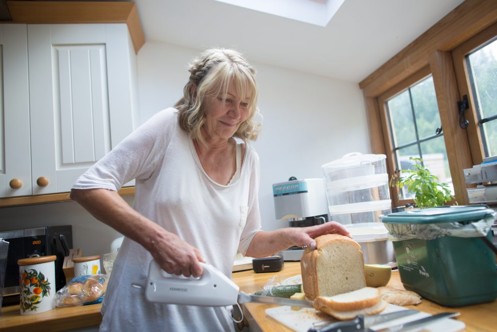 brides mum cutting bread in kitchen
