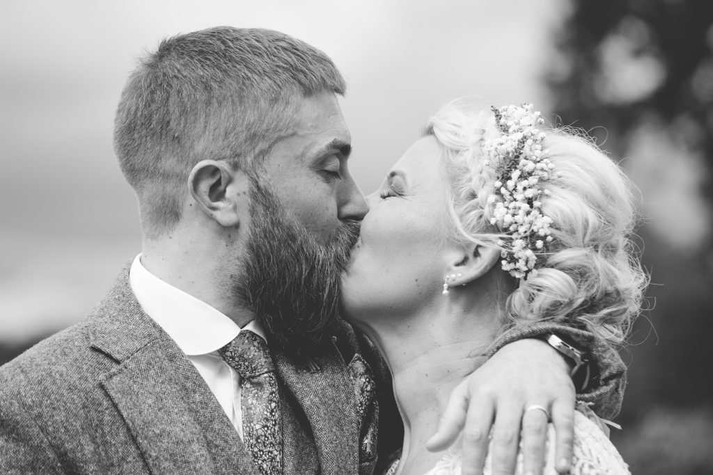 black and white photo of bride and groom kissing during ceremony