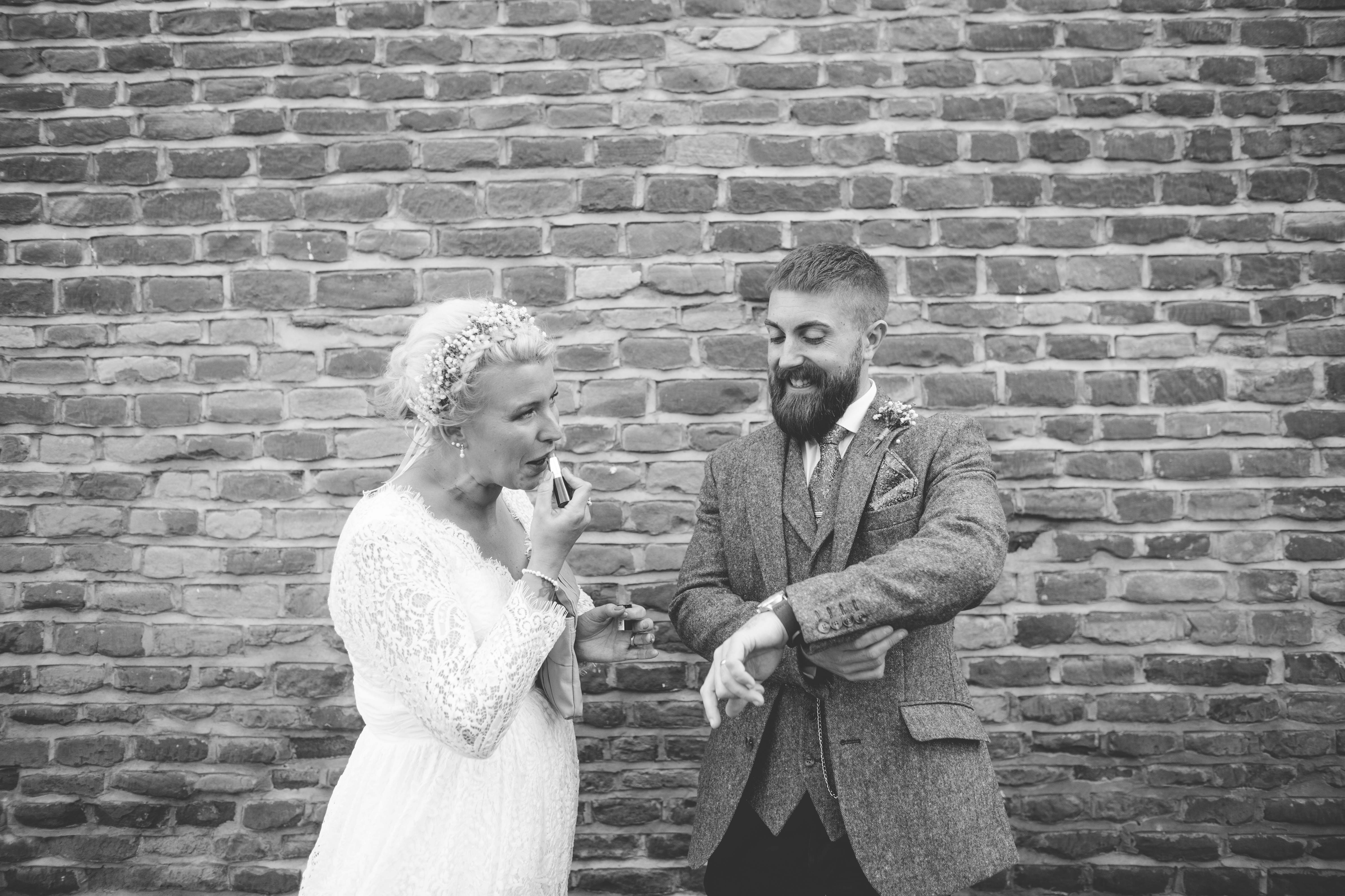 Black and white photo of groom looking at watch and bride applying lipstick