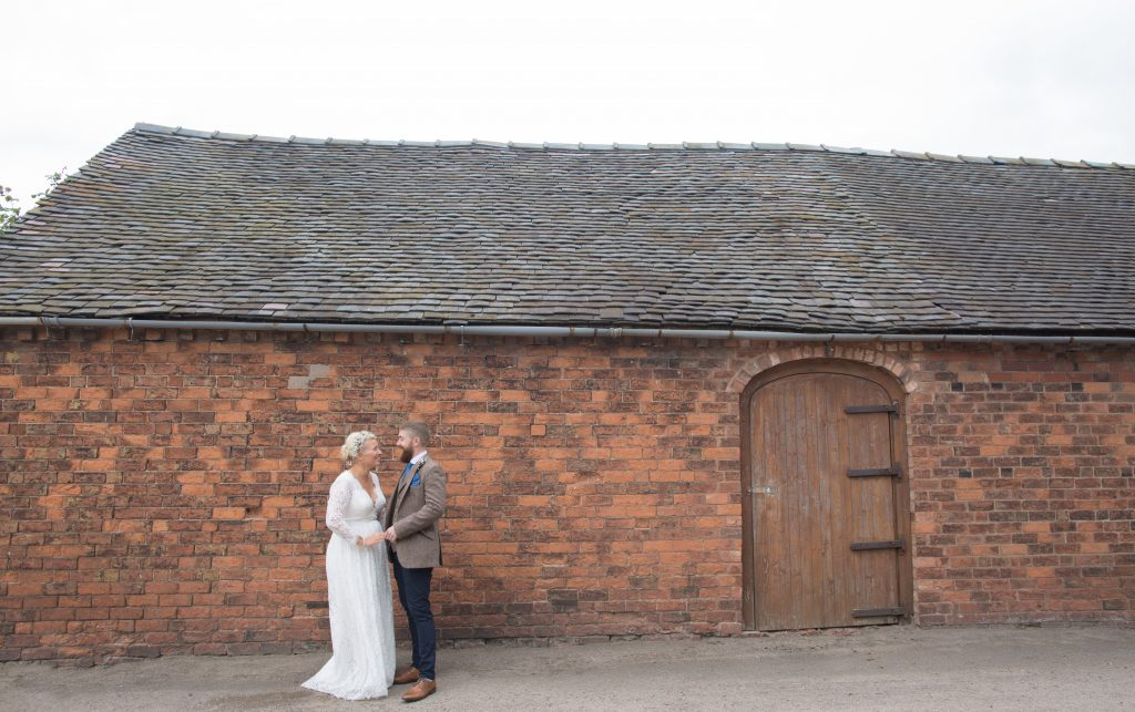 bride and groom stood in front of brick wall