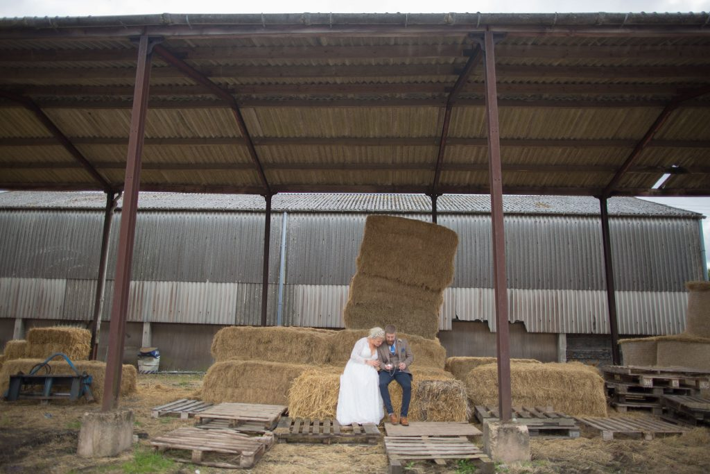 bride and groom sat on hale bales on farm in staffordshire