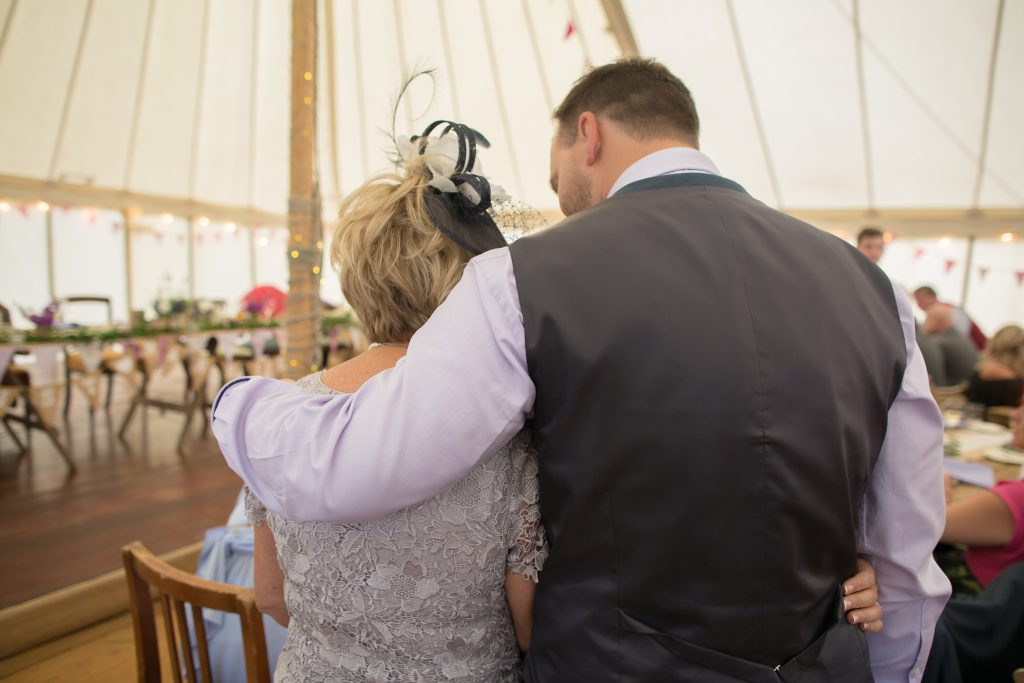 photo of brother with arm round mother of the bride
