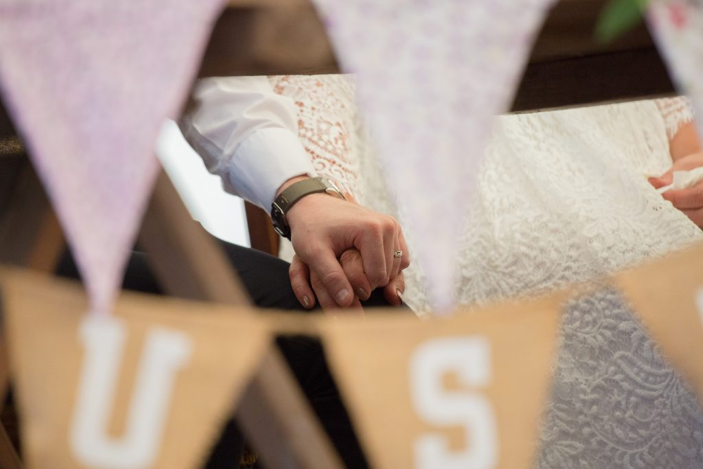 photo of bride and groom holding hands under table