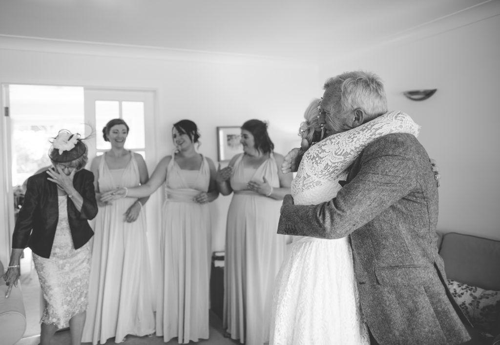black and white picture of bride hugging Dad
