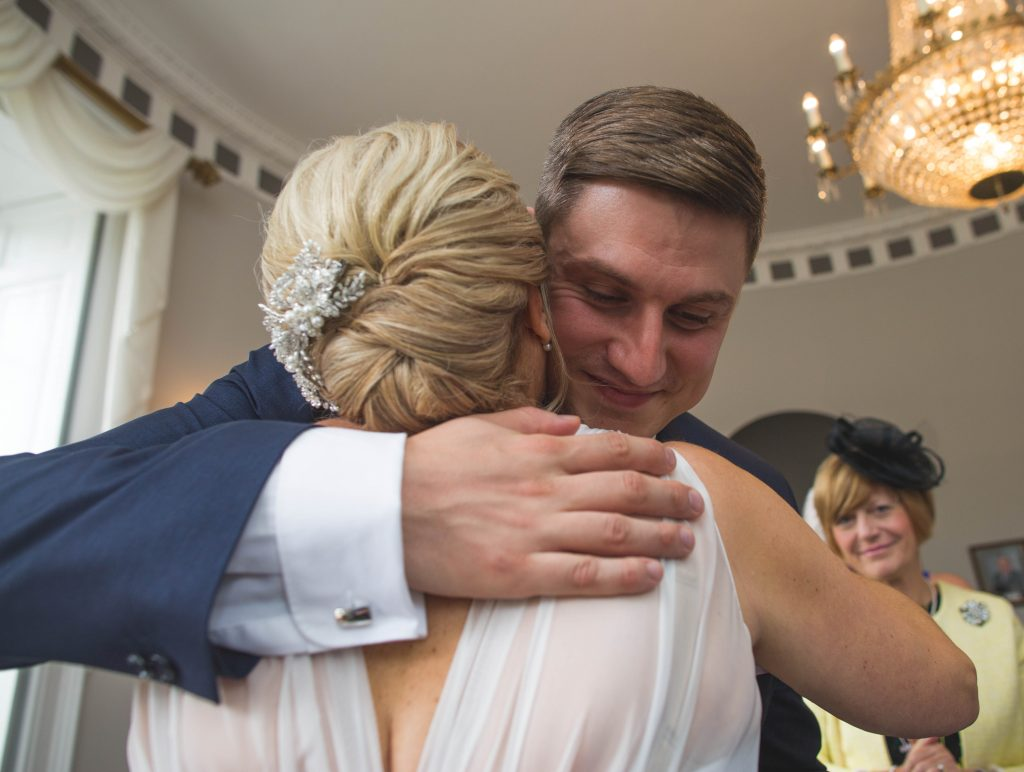 son hugging his mum after she has just got married