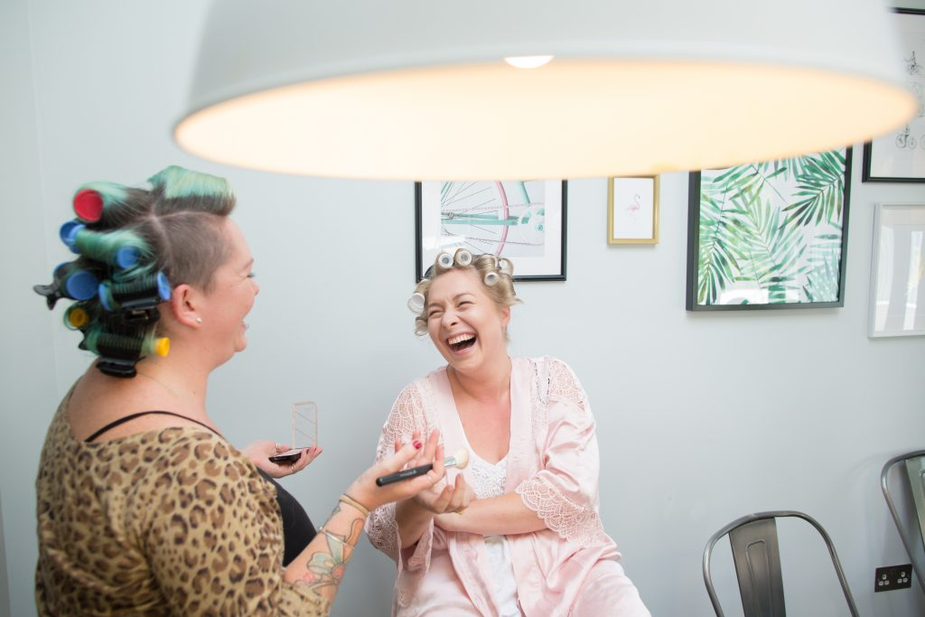 bride laughing with make up artist