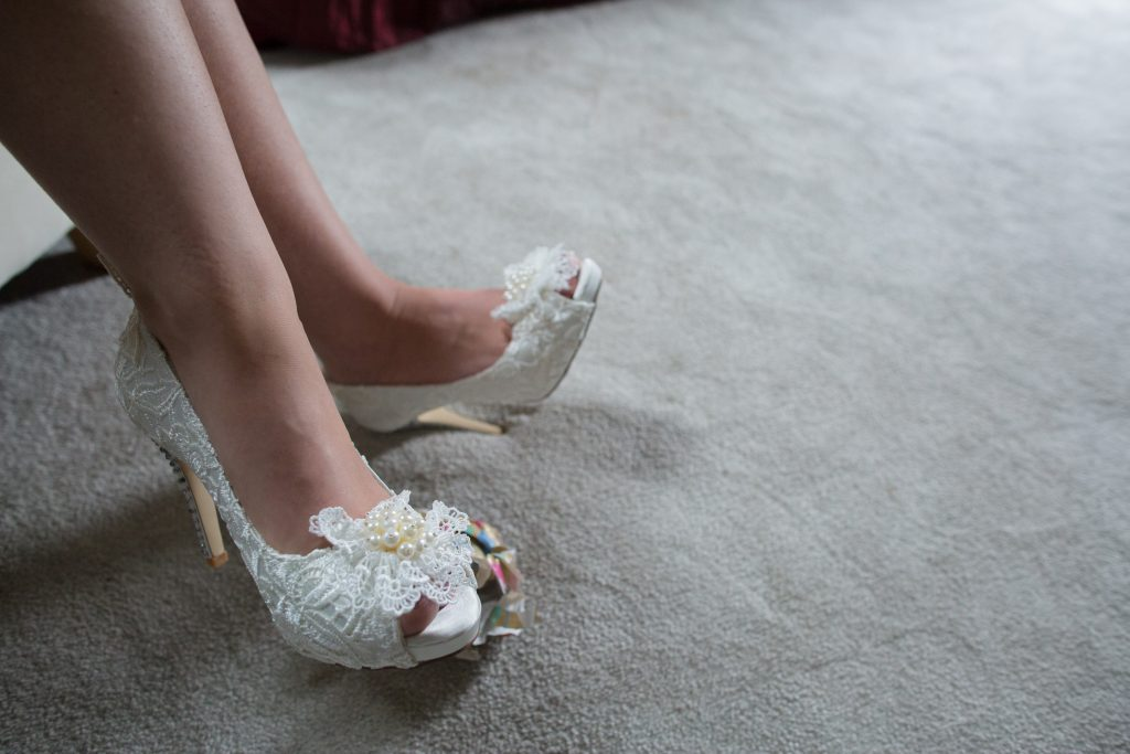 close up of bride wearing wedding shoes