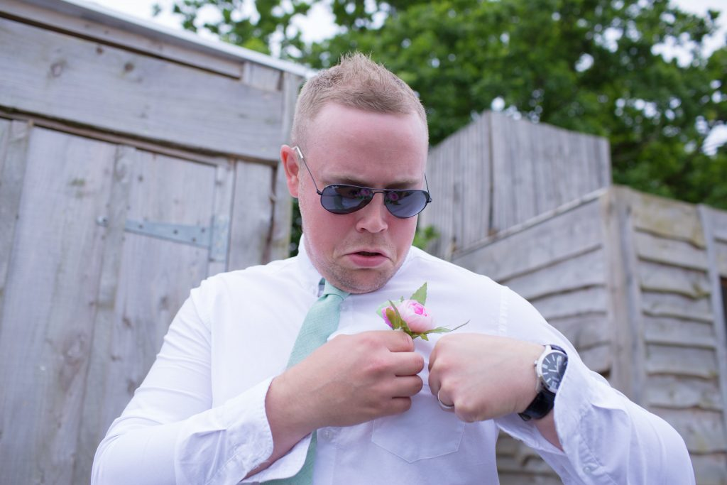 best man trying to attach buttonhole