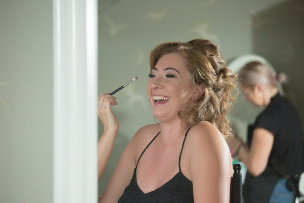 maid of honour laughing whilst having make up done