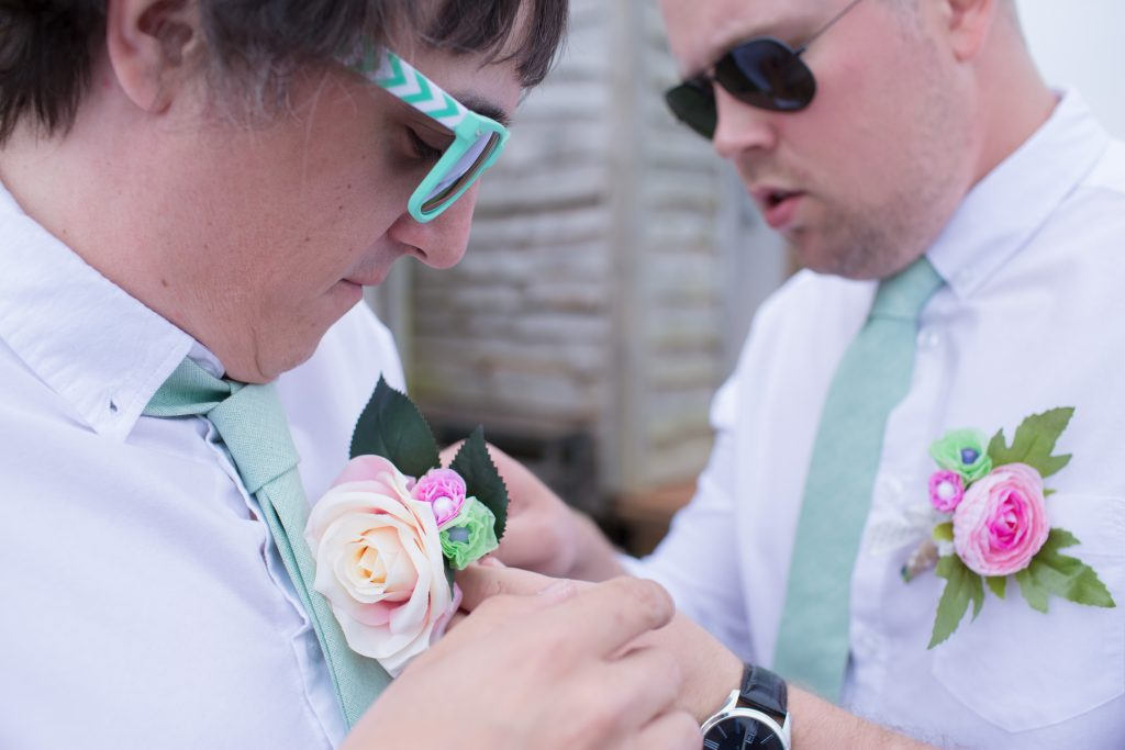 groom having help with button hole from best man