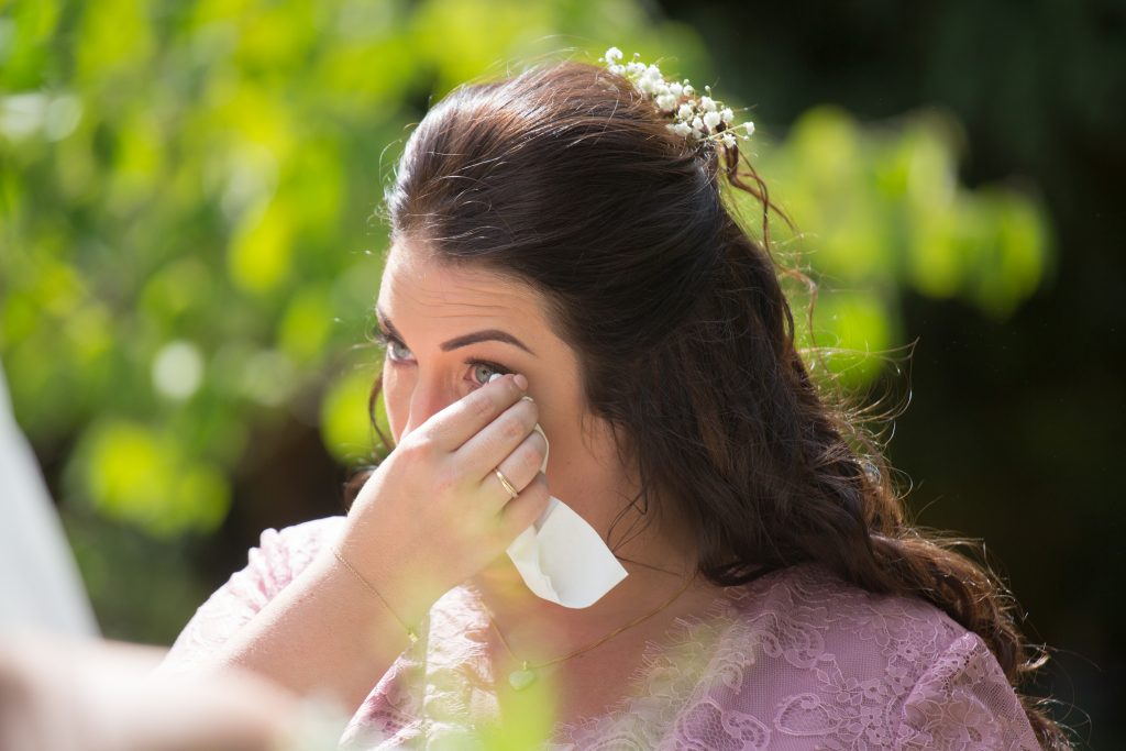 close up photo of brides sister crying