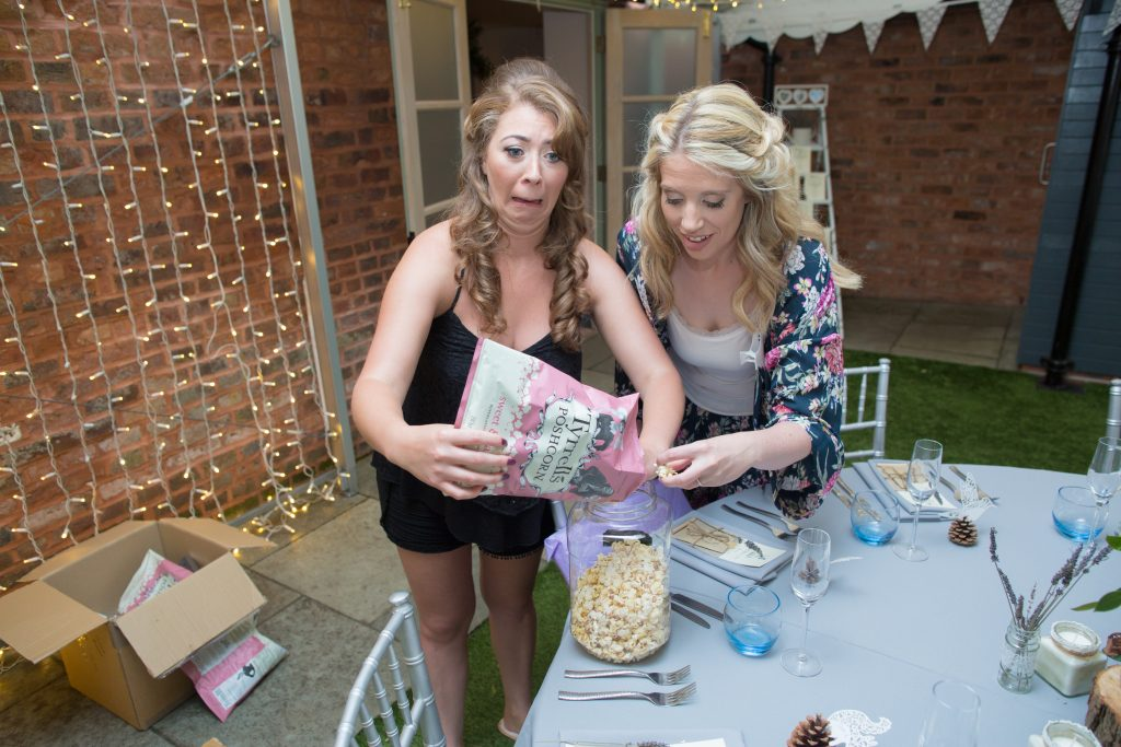 maid of honour and bridesmaid putting popcorn out
