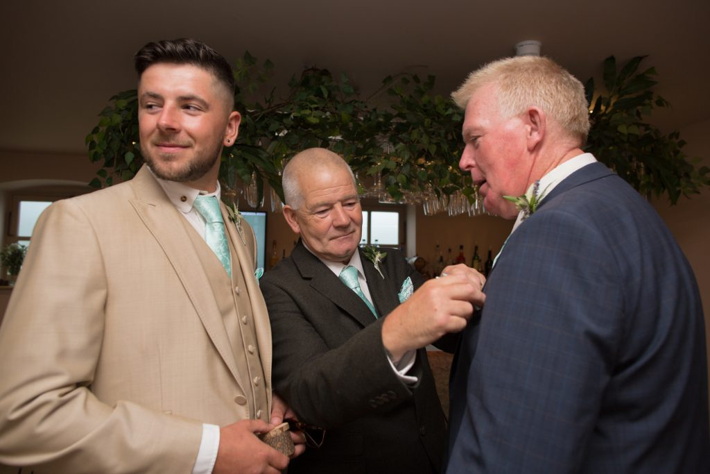 father of groom putting buttonhole on