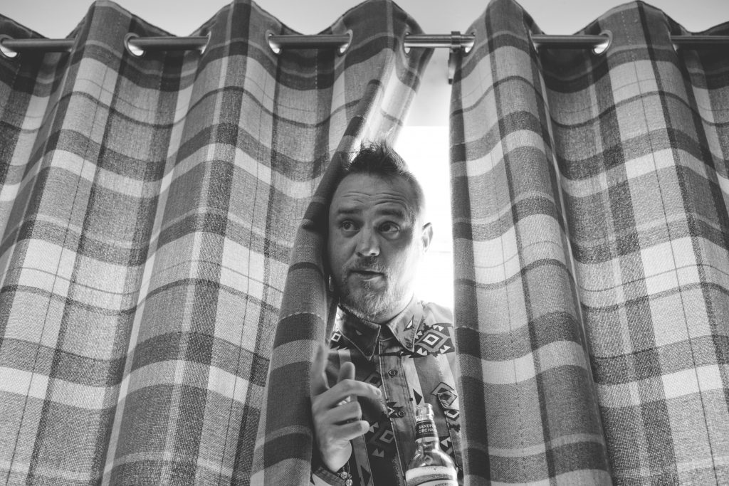 black and white picture of man poking head through curtains