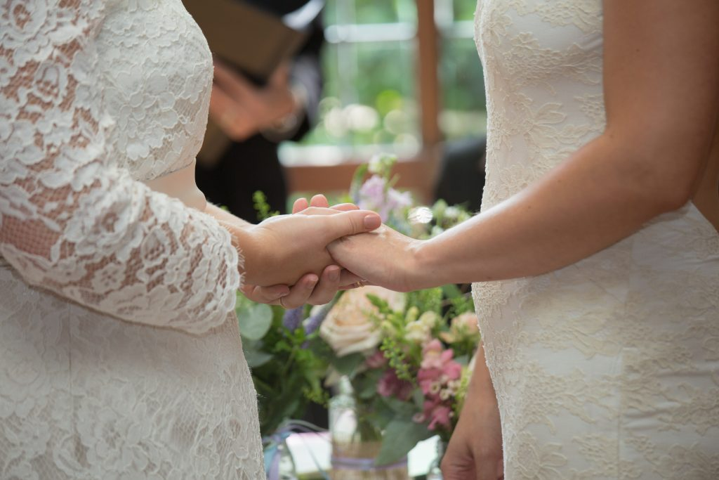 close up of two brides holding hands during wedding ceremony