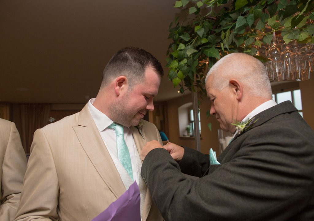 groom having help from his dad on morning of wedding