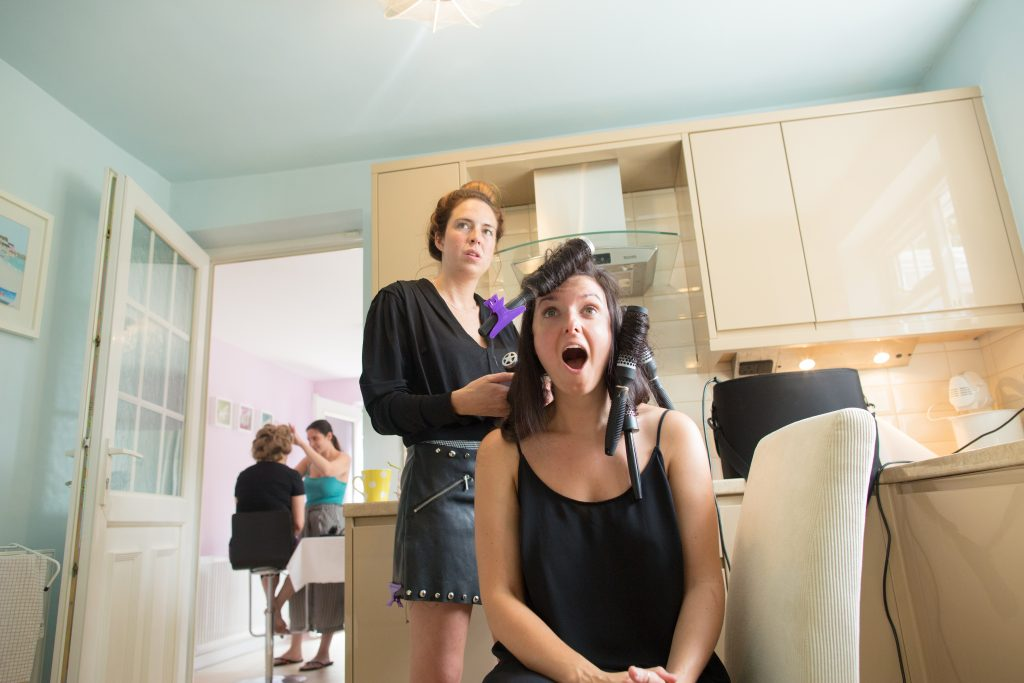 bride with hairbrush in hair during prep