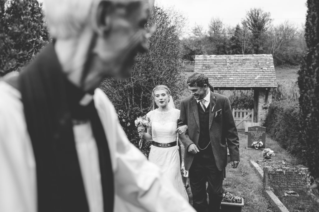 vicar, bride and dad walking up to church