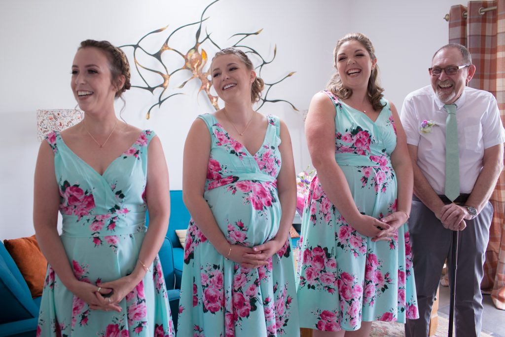 bridesmaids and father of bride reaction to seeing bride in wedding dress
