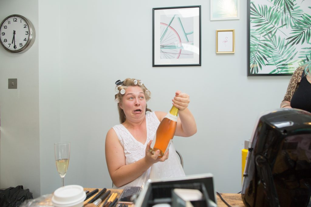 bride pulling funny face whilst opening bottle of fizz