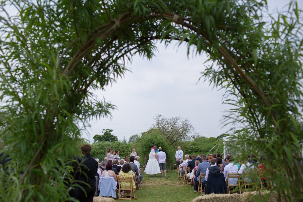 photo taken through archway of couple during wedding ceremony
