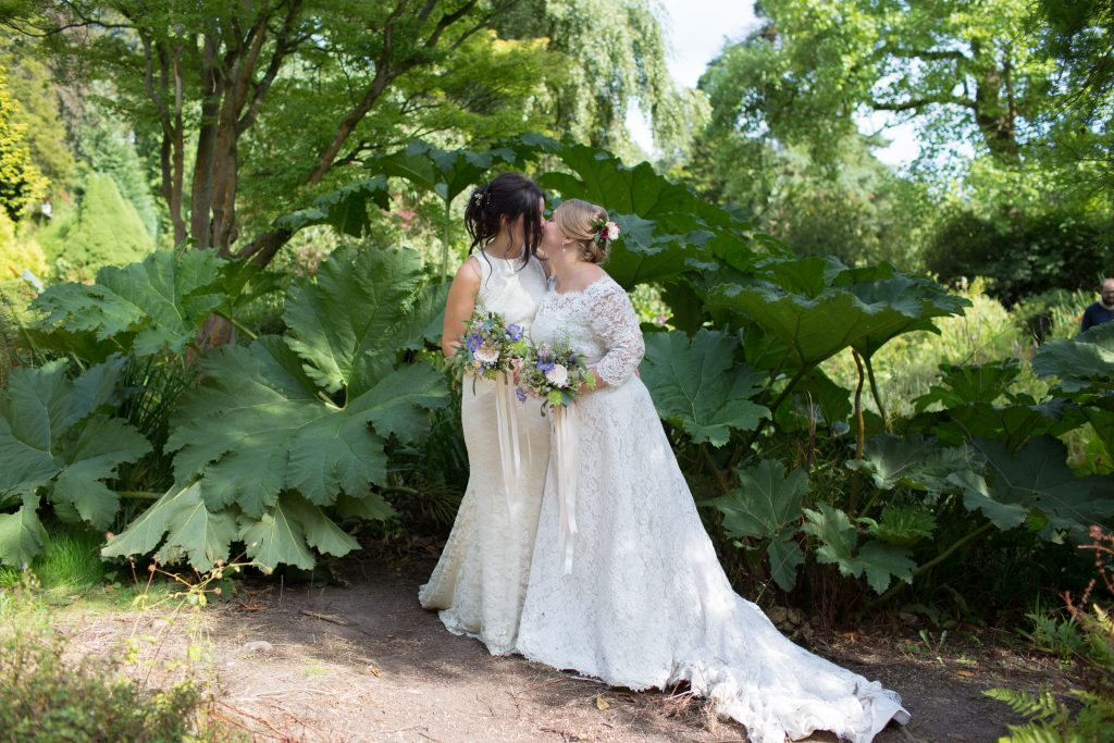wedding photo of two brides standing in front of gains rhubarb