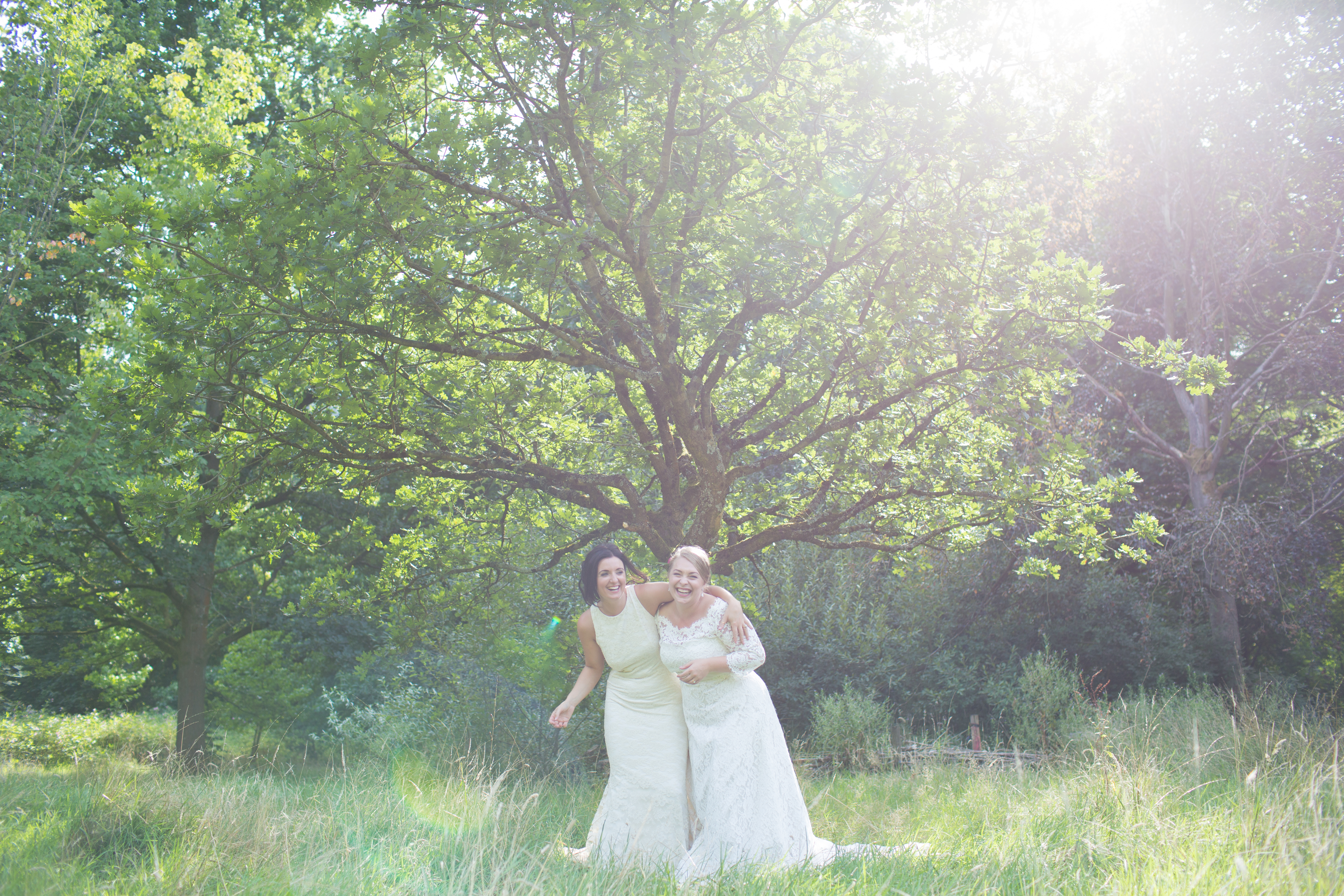 two brides laughing stood in front of a tree in the sun