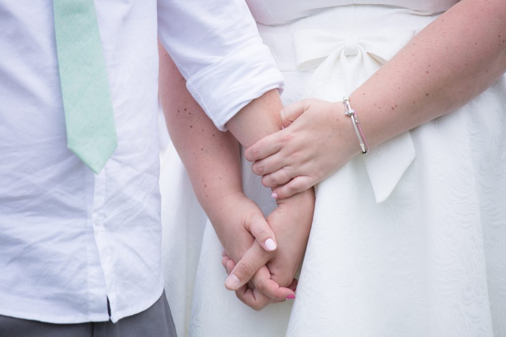 close up photo of bride and groom holding hands during ceremony