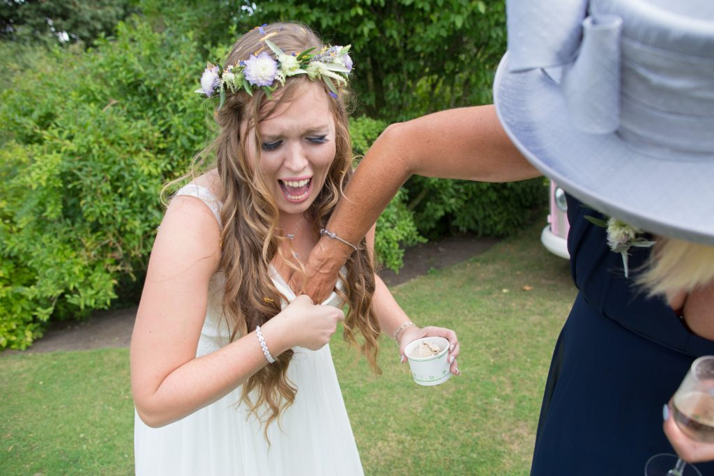bride having confetti removed from down her wedding dress